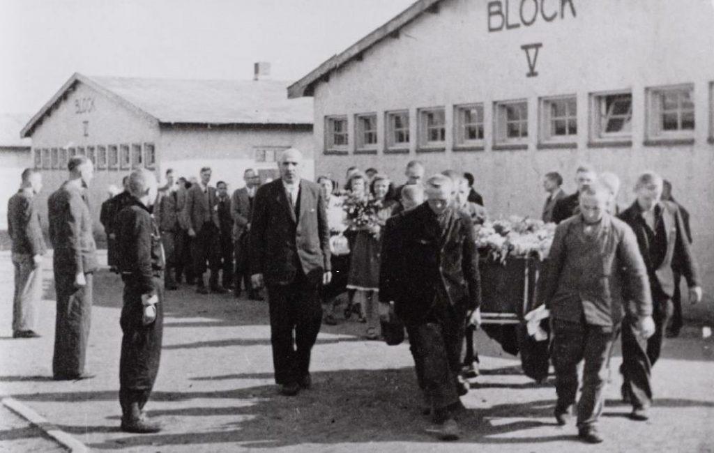 Vader Sixma lopen naast de baar van een overleden verzetsman in Kamp Amersfoot